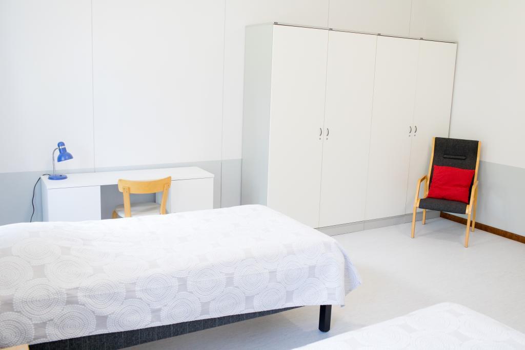 Kuvassa Otavan Opiston opiskelija-asuntolan huone, jossa sänky, nojatuoli, kirjoituspöytä ja säilytystilaa.